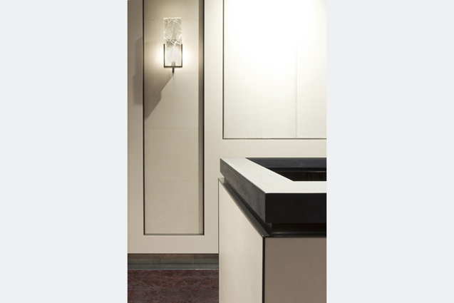 investment firm fabric wall panel crystal sconce reception desk detail