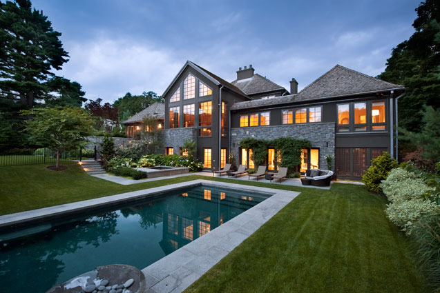 Stone redesigned exterior facade view from in-ground pool and serene landscaped yard